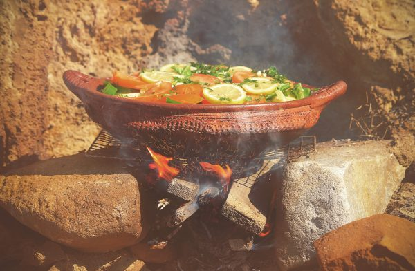 Ceramic dish with vegetables on fire