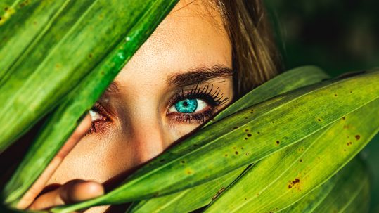 Women with green eyes looking from behind leaves