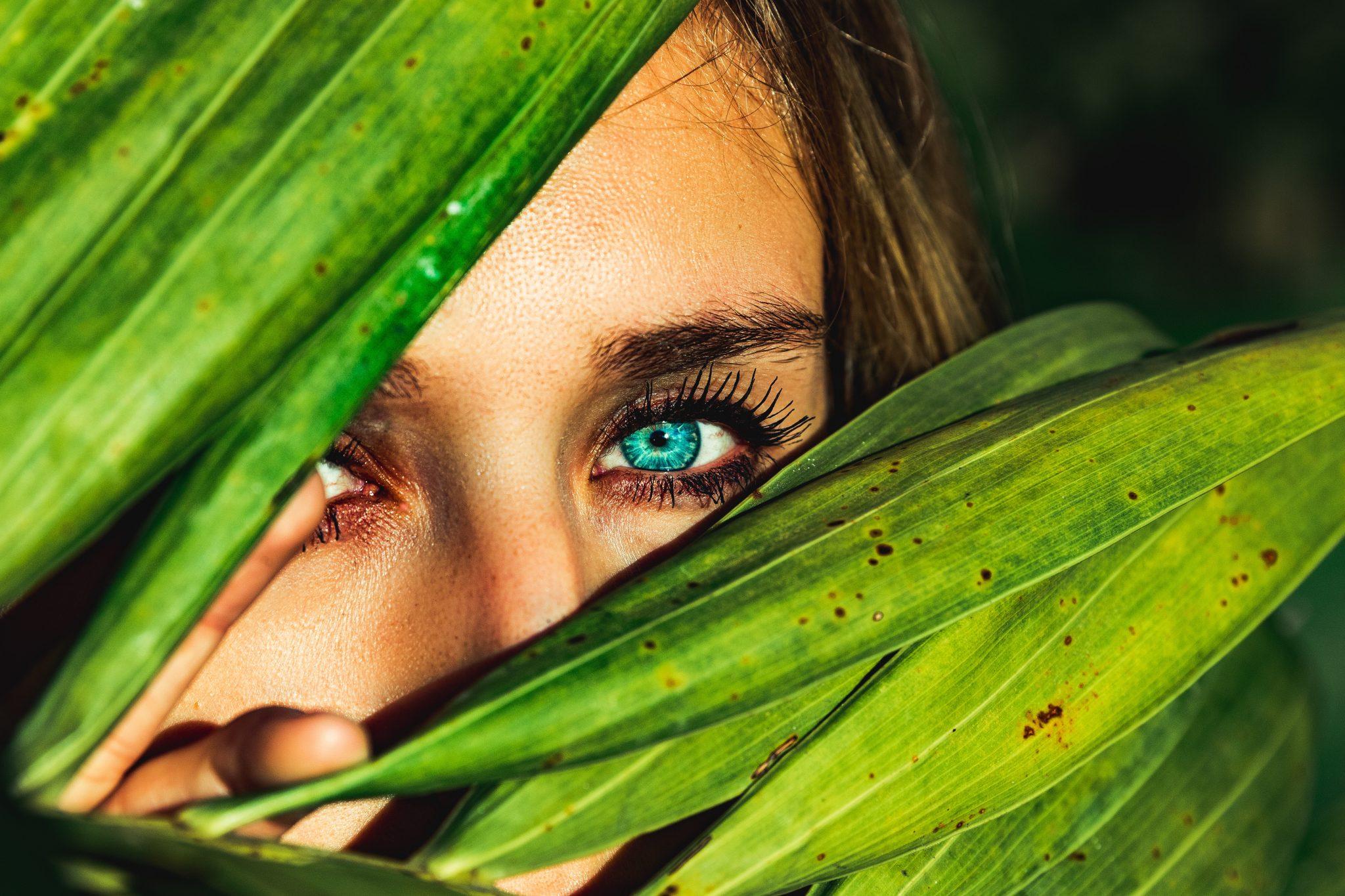Mujer mostrando ojos entre plantas de ayurveda
