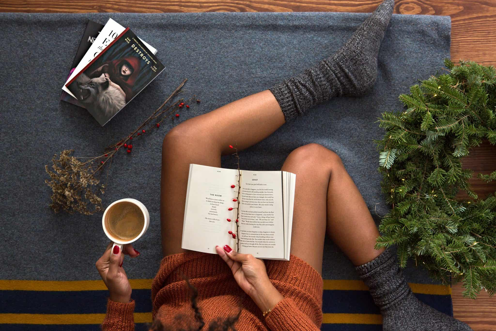 Female sitting on blanket with cup of coffee and book