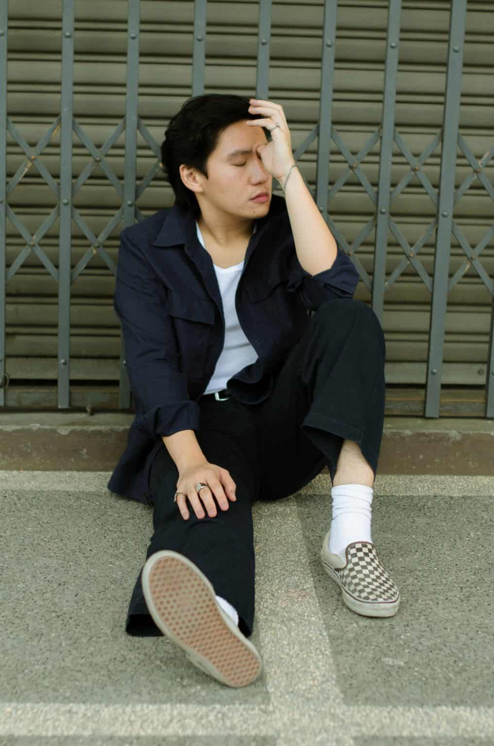 Young Asian man sitting on ground against fence hold head with eyes closed