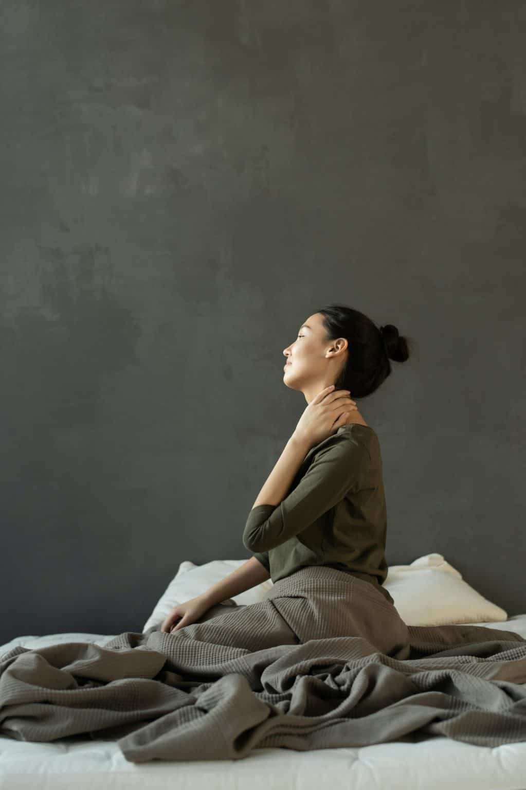 Young Asian woman sitting on bed with hand in neck