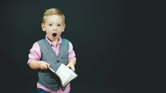 Little boy holding book looking surprised.