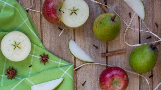 Cut apples and pears on wooden table