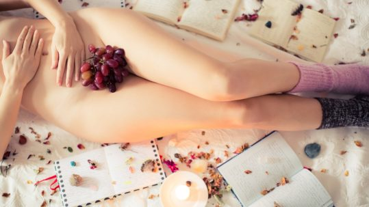 Woman laying down with grapes on belly and surrounded by flowers and notebook.